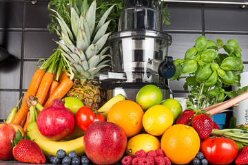 slow juicer in kitchen with many fruit and vegetable juice healthy lifestyle concept background