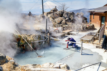 A man boiling black eggs in sulphuric hot spring, Owakudani, Hakone, Kanazawa. Fuji mountain in the...