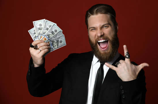 Bearded business man lucky guy in black suit holds American dollars hundreds banknotes shows rock sign cool sign and showts