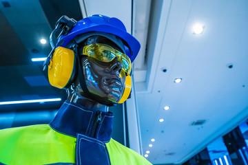 Protective equipment on a mannequin. Specialist clothes. Protective helmet. Antinoise headphones. Protective glasses. Personal protective equipment. Safety at work. Wall mural