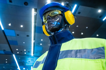 Protective gear on a mannequin. Specialized working clothes. Protective helmet. Headphones against noise. Protective glasses. Personal protective equipment. Industrial safety. Wall mural