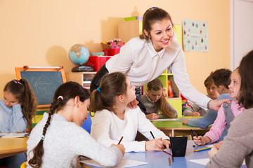 Teacher helping children drawing