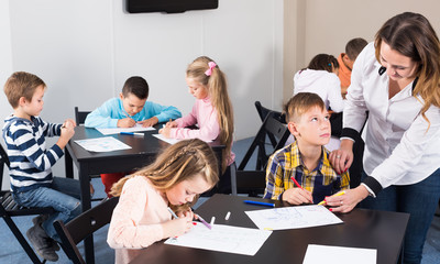 Little children with friendly teacher drawing in classroom