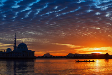 Black silhouette of people training for Dragon boat regatta in Kuching, mosque on Sarawak river with colorful sunset background. Traditional culture, travel destinations on Borneo island in Malaysia.