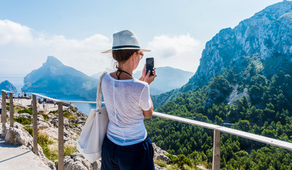 Back view of a woman taking photograph with a smart phone camera. Pretty female  tourist is taking pictures of the Mountain.