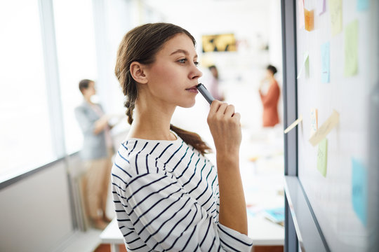 Side view portrait of contemporary young woman drawing on whiteboard in office and thinking, copy space