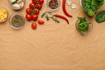 Ingredients and spices for homemade pizza on wooden table