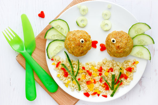 Fish meatballs with porridge and vegetable slices for funny and healthy dinner for kids, food art composition