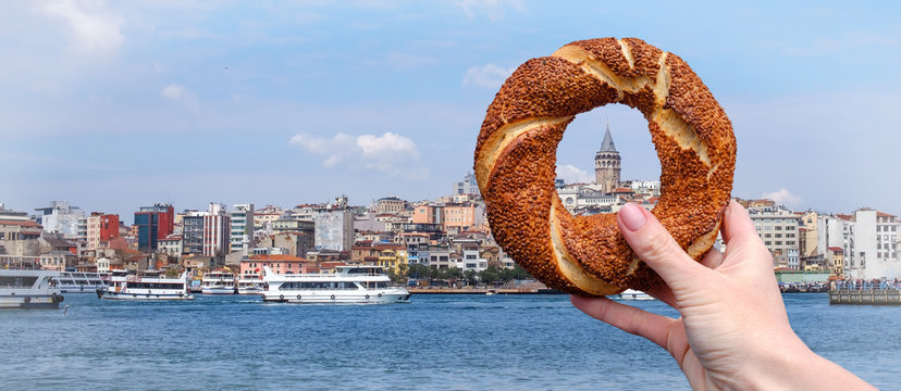 Traditional Turkish bagel simit in a female hand on the background of the panorama of Istanbul and the Galata Tower, horizontal banner