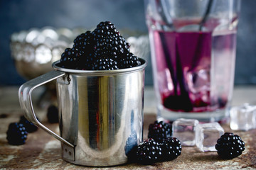 Juicy fresh ripe blackberry in cup and refreshing blackberry drink with ice cubes behind