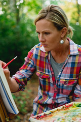 Female painter creating watercolor painting in forest, Neenah, Wisconsin, USA