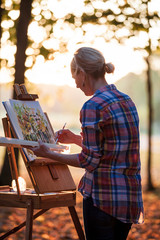 Woman in checked shirt painting with watercolors in forest at dusk, Neenah, Wisconsin, USA