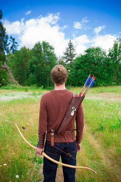 Portrait of a young adult male with archery gear outdoors