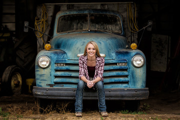 Attractive young woman sitting on the bumper of an old truck