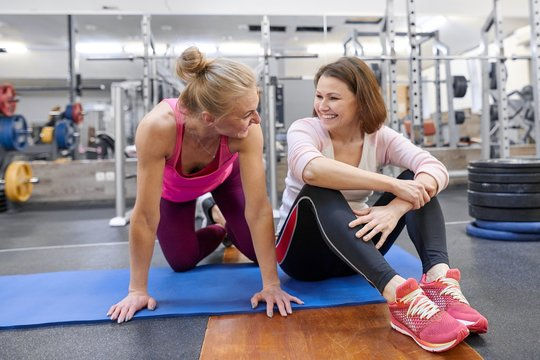 Fitness instructor and mature woman at gym. Female sports instructor and middle-aged woman talking smiling and laughing in health club