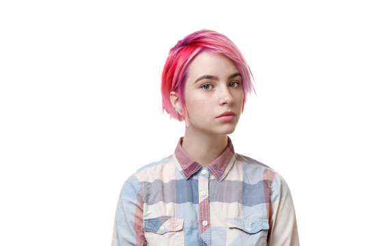 Young beautiful girl with a short hair cut pixie bob. Color hair coloring, red pink color. Shirt in a cellar, casual style.