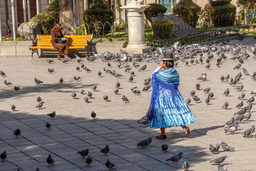 Bolivian woman cholita in blue dress and retro hat walking across La Paz central square full of pigeons, Bolivia