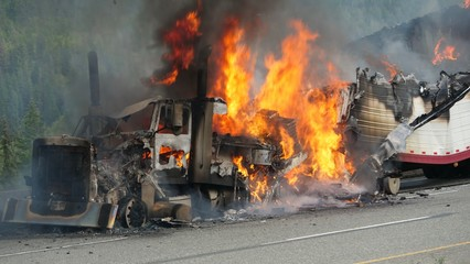 A semi truck burns out of control on a highway