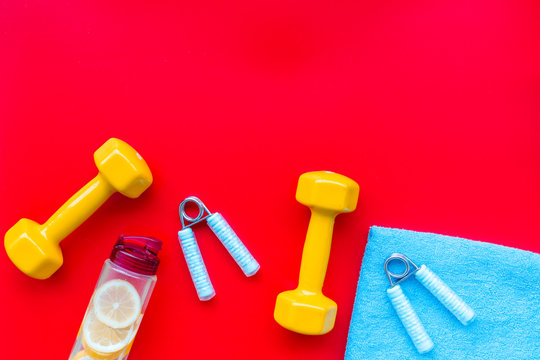 Fitness set with bars, towel, bottle of water and wrist builder on red background top view mock up
