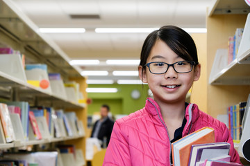 Teenage Asian girl with eyeglasses standing with books in the library