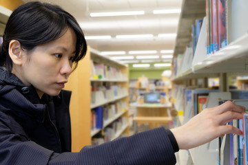Portrait of serious Asian lady in library looking for a book