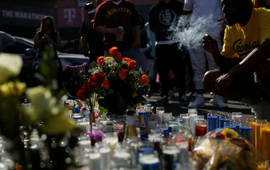 A person smokes by a makeshift memorial for Grammy-nominated rapper Nipsey Hussle who was shot and killed outside his clothing store in Los Angeles