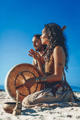 beautiful young couple playing ethnical music with shaman drums outdoors