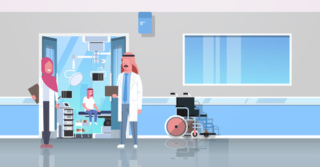 arab doctors discussing in hospital corridor with wheelchair open door to surgery room arabic man sitting operating table modern clinic interior flat full length horizontal banner