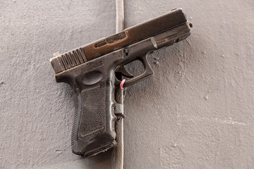 Close-up  plastic toy gun made of plastic fastened with a yoke to the old wall
