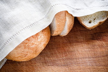 Fresh bread under a linen napkin on a woodenFresh bread under a linen napkin on a wooden