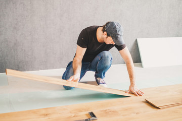 Adult man lays the laminate panel on the substrate with the technology