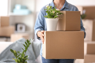 Woman with moving boxes and plant in room