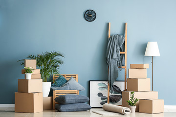 Belongings and moving boxes near wall in room