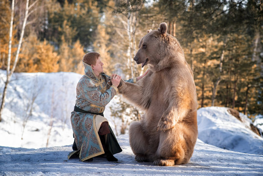 A man in traditional national costume of a Russian prince sits on one knee and holds a brown bear by the paw in a winter forest.