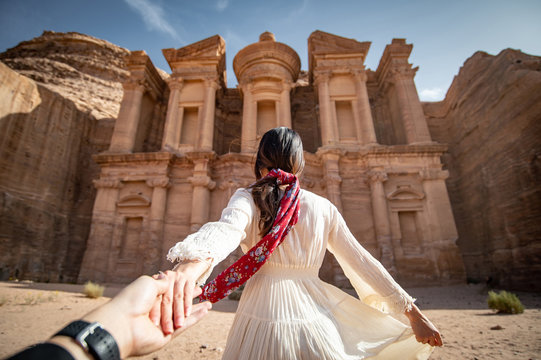 Asian woman tourist in white dress holding her couple hand at Ad Deir or El Deir, the monument carved out of rock in the ancient city of Petra, Jordan. Travel UNESCO World Heritage Site in Middle East