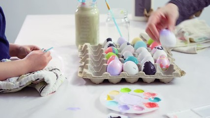 Wall Mural - Little girl painting craft Easter eggs with acrylic paint.