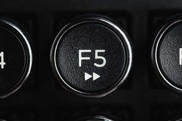 A close-up or macro shot of the round F5 key of a black antique style typewriter keyboard in horizontal image format.