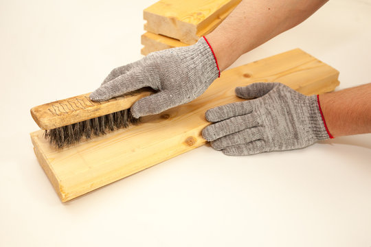 Hand wire brush men's hands in protective gloves on vintage wooden Board. Aging wooden boards by brushing. White background. Create fotofone