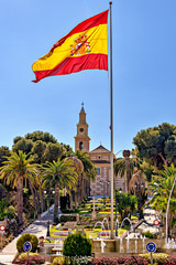 Spanish flag flying with church, city park background.