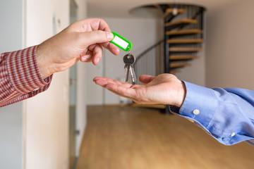 Der Wohnungsschlüssel wird übergeben, im Hintergrund ist eine leere Maisonette Wohnung zu sehen