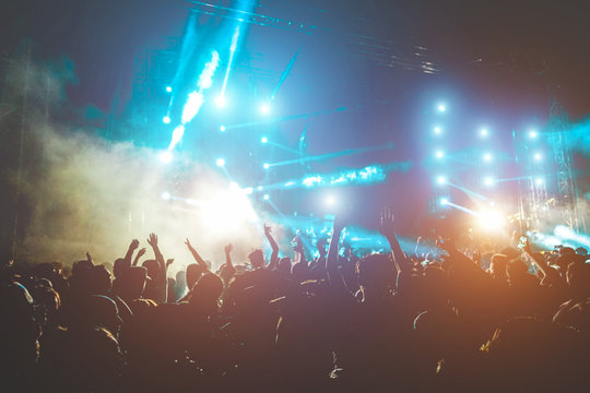 Happy people dancing and having fun in summer music festival party outdoor - Soft focus on center hand up with blue flare - Fun and youth concept