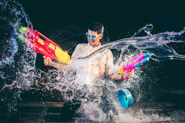 Young Asian men are laughing fun on Songkran Festival. He was holding a large squirt guns in both hands, and in the midst of the water is splashed out around the direction. On a black background.