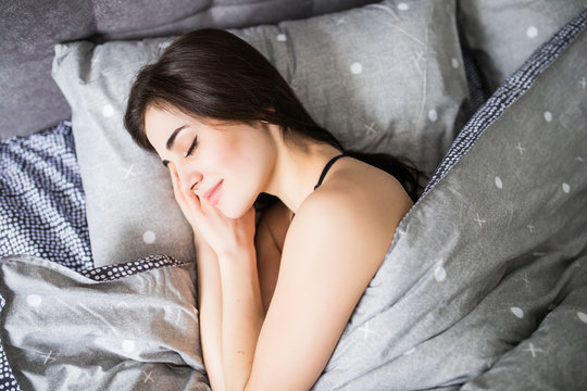 Top view of attractive young woman sleeping well in bed hugging soft white pillow. Teenage girl resting, good night sleep concept.