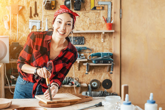 Asian Woman craftsman creates wood products for sale in her shop. Handmade and design concept