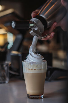 the process of preparing a delicious coffee drink with whipped cream that is decorated with coffee with milk