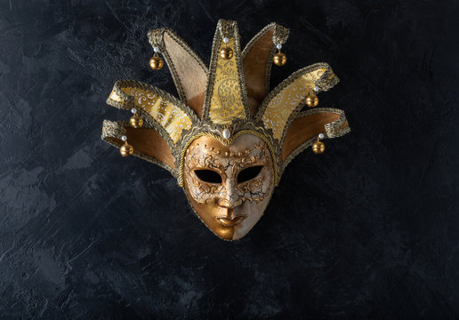 Venetian mask on a black background. Gilded mask on a stone black wall background.