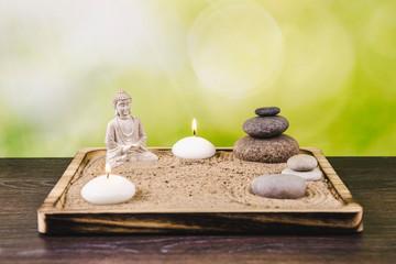 Obraz Miniature desk zen sandbox with Buddha figure sit in Lotus position, stacked zen sea stones, spa candles burning against green bokeh studio background, copy space. - fototapety do salonu