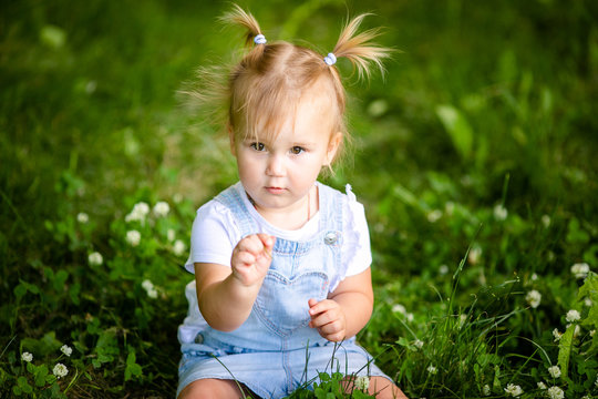 Happy funny blonde baby girl with two little braids in white t-shirt and jeans bodykit sitting on green grass background