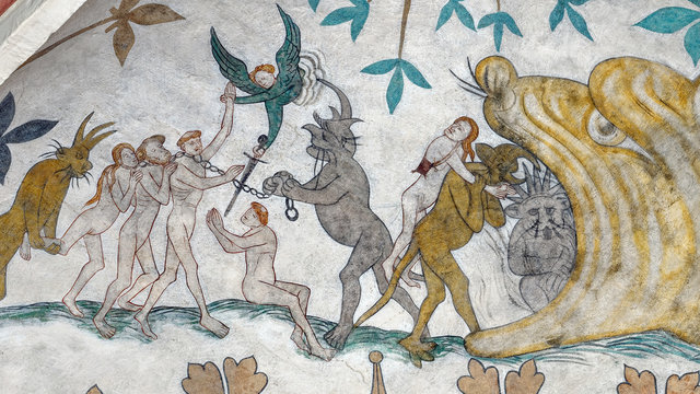 Medieval hell scene from Odsherred Church in Denmark. An angel is fighting the chains of the demons dragging sinners  into the flaming jaws of hell where the devil himself resides