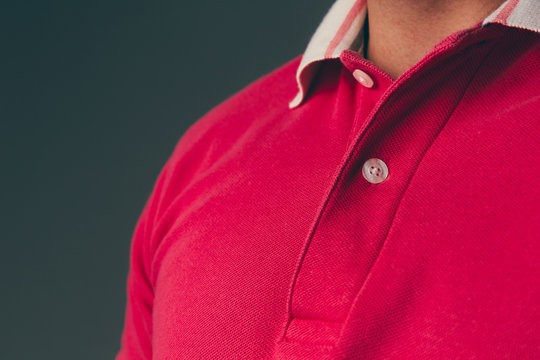 Close up of a young adult caucasian male wearing a red polo shirt